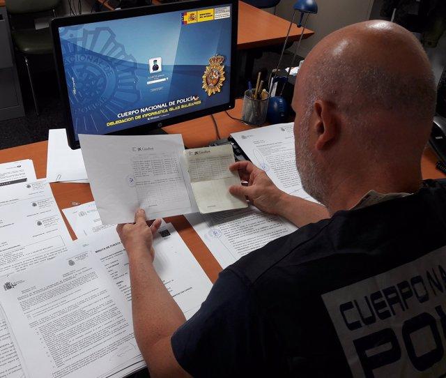 Un agente de la Policía Nacional estudia movimientos bancarios tras la denuncia