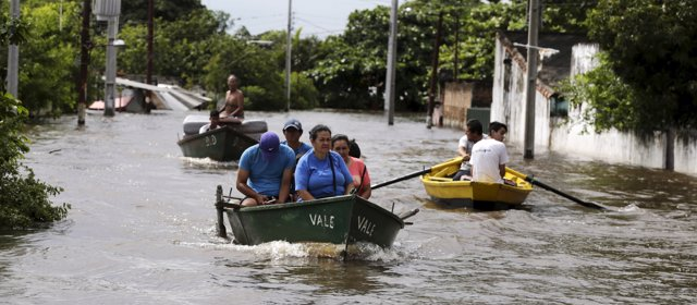 People travel on a boat near flood-affected houses in Asuncion, December 27, 201