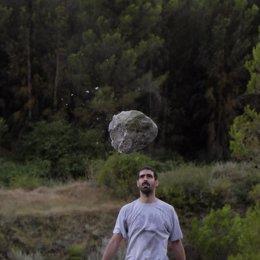 El artista, Alberto Oderiz, con el material, la piedra