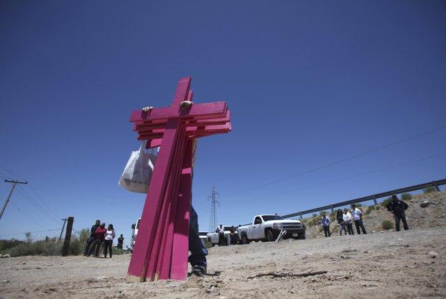 Un hombre sujetando cruces rosas por el abuso sexual en México