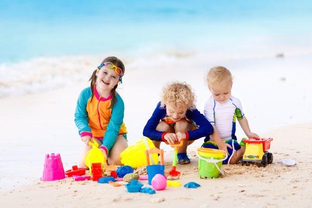 Niños jugando en la arena de la playa