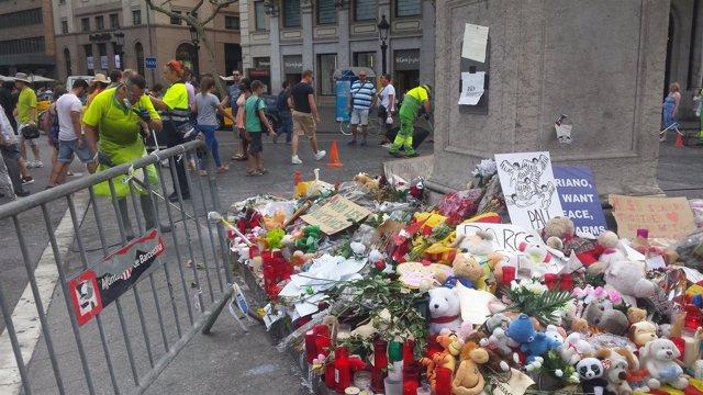 Altar por los atentados al inicio de La Rambla con operarios limpiando el suelo