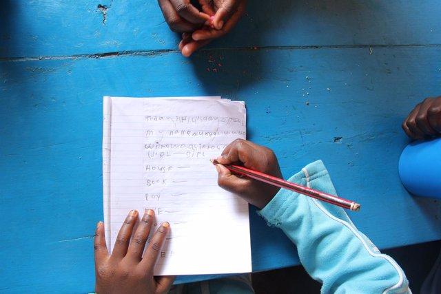 Una niña refugiada escribiendo en Uganda