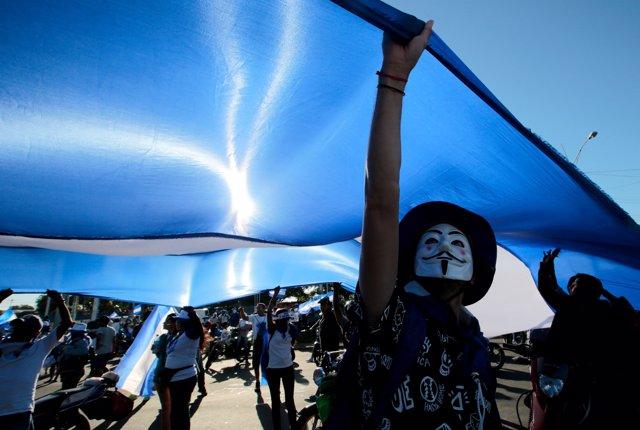 A masked demonstrator holds a big national flag during a protest against Nicarag
