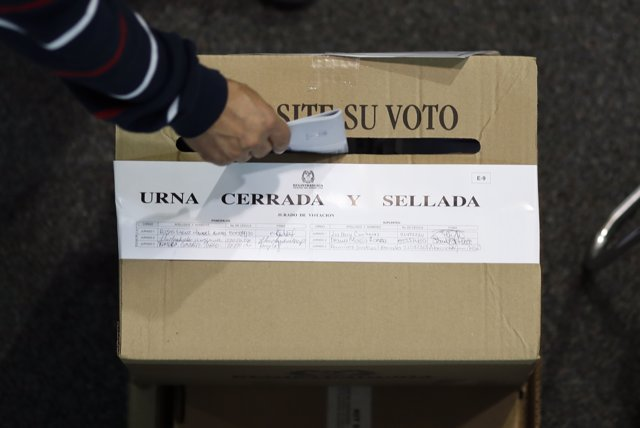 A man drops his ballot into a box at a polling station set up at a convention ce