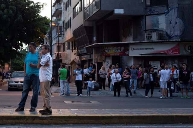 People stand on the street after an earthquake struck the northern coast of Vene