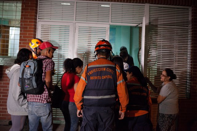 Venezuelan Civil Protection members help evacuees return to the building of the