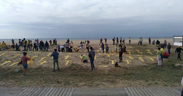 Imagen de archivo de cruces amarillas con toallas en la playa de Mataró