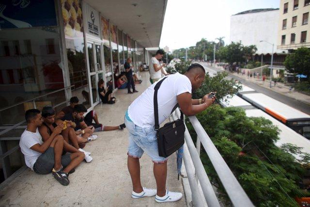 Cubanos en un puesto público de conexión WiFi