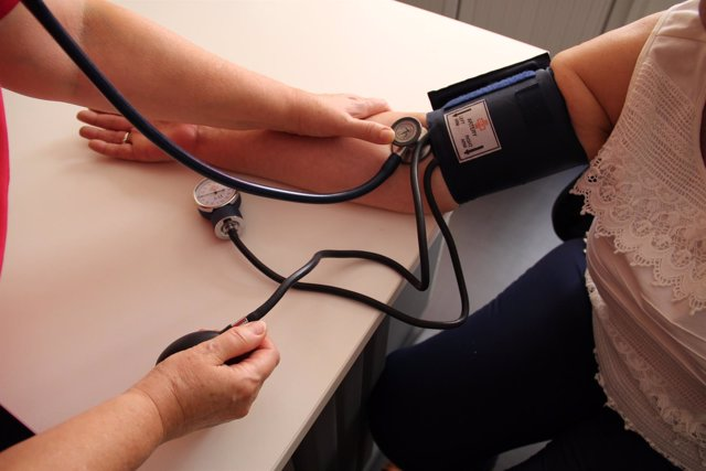 Una persona se mide la tensión, tensiómetro
