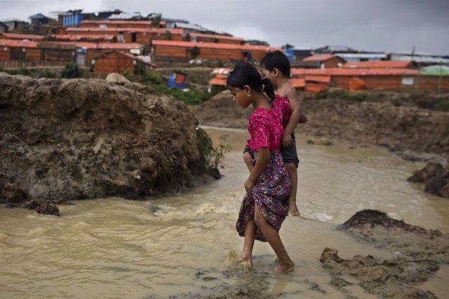 Una niña lleva a su hermano en un campo de refugiados rohingya en Bangladesh