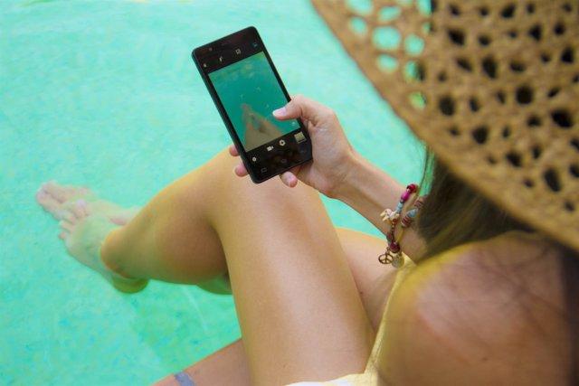 Una mujer usa el móvil en la piscina
