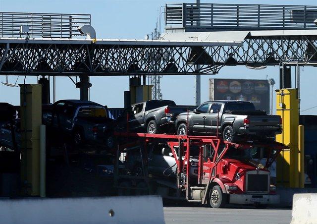 Camiones en la frontera entre México y EEUU transportan vehículos