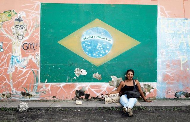 Una mujer venezolana junto a la bandera de Brasil en Roraima