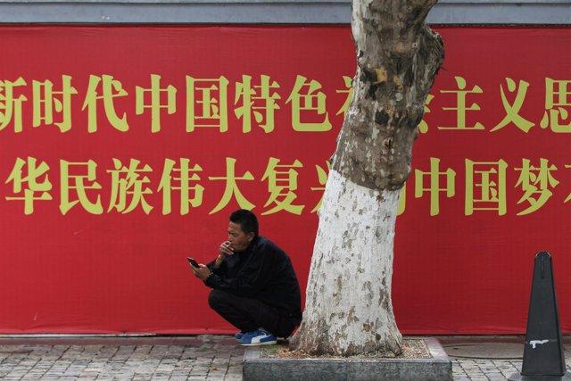 Un hombre mira su teléfono móvil frente a un cartel propagandístico