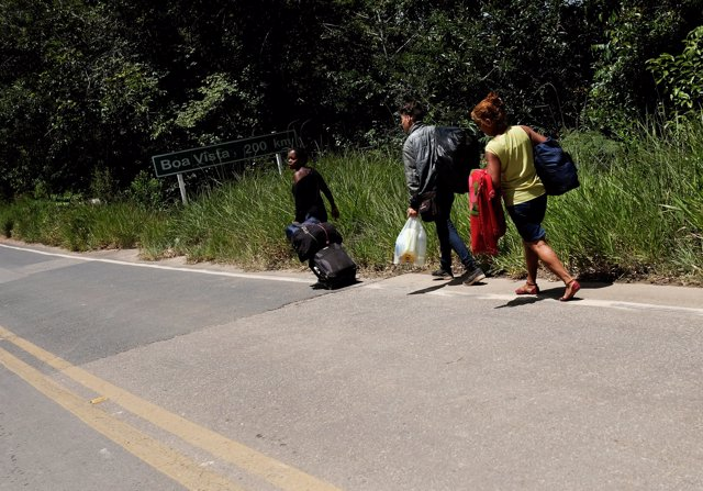 Venezuelans walk and attempt to hitchhike toward Boa Vista city, after they obta