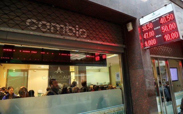 People are seen inside a currency exchange store in Buenos Aires' financial dist