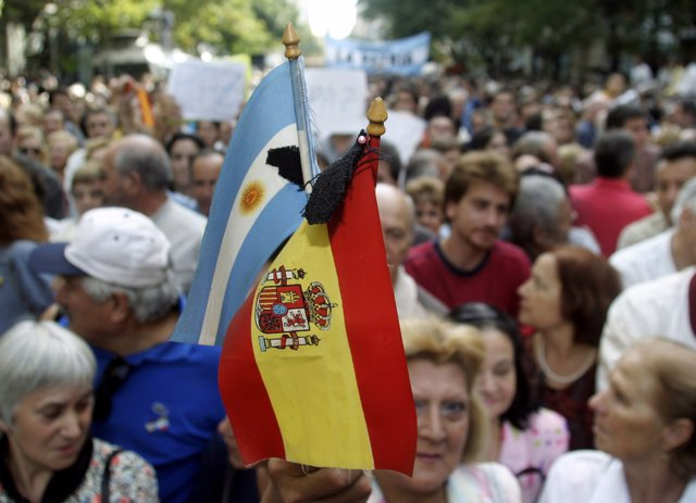 A protester holds Spanish and Argentine flags in Buenos Aires to mourn the victi