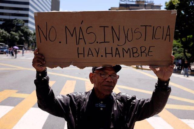 "A man holds a placard that reads ""No more injustice. There is hunger"" during a r"