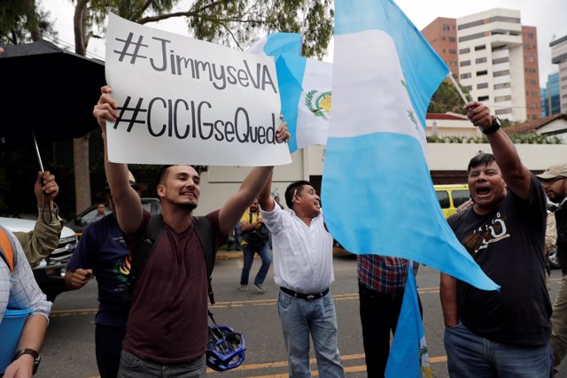 A demonstrator (L) holds a sign as he protests against Guatemalan President Jimm