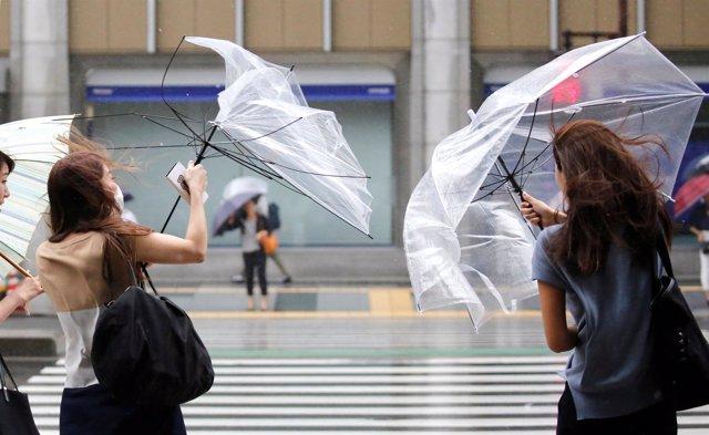 Unos peatones intentan controlar su paraguas ante el fuerte viento en Tokio