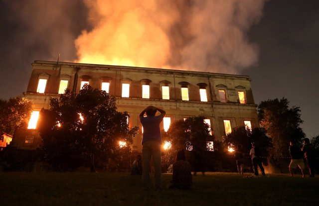 People watch as a fire burns at the National Museum of Brazil in Rio de Janeiro,