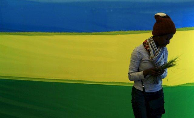 Una mujer delante de una bandera de Ruanda