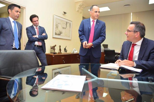 El delegado del Gobierno firma el documento en presencia dle rector