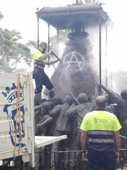 Un operario limpia la pintada en el Monumento de la Virgen del Rocío.