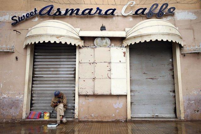 Un limpiabotas sentado frente a una cafetería en Asmara