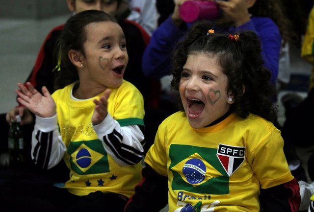 Students watch the broadcast of the World Cup Group E soccer match between Brazi