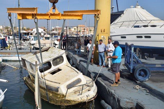 Trabajos de extracción de una embarcación semihundida en el Mar Menor