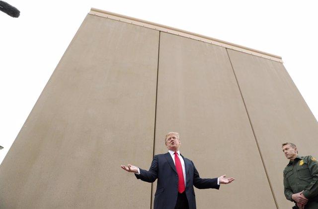 Donald Trump junto a un prototipo de muro para la frontera con México