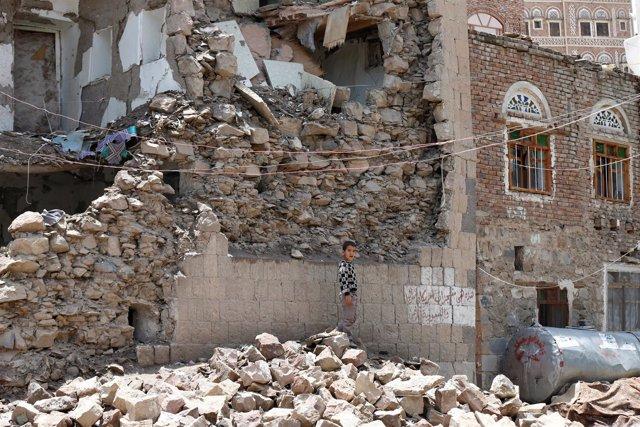 Un niño entre los escombros de una casa destruida en un bombardeo en Saná