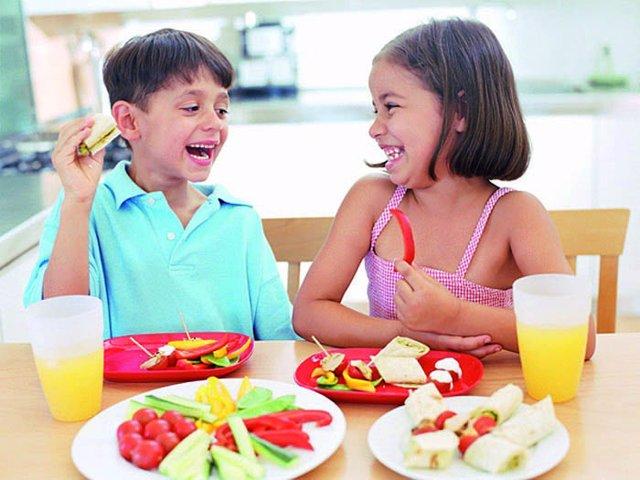 Niños comiendo frutas y verduras