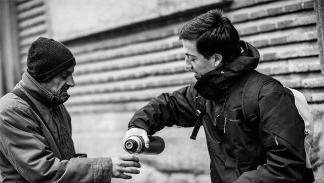 Joven voluntario sirve café a una persona sin hogar