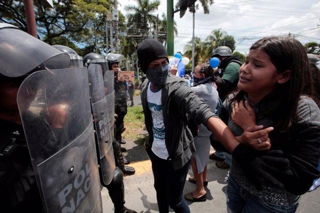 Manifestante frente a policía antidisturbios en Managua.