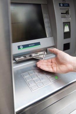 Persona retirando efectivo de una sucursal bancaria