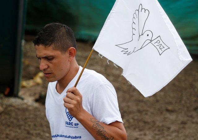 Guerrillero de las FARC sostiene una bandera con la paloma de la paz