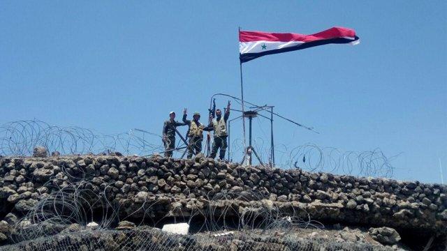 Soldados izan la bandera de Siria tras tomar una colina en Quneitra