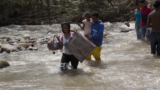 Venezolanos cruzan un río fronterizo con Colombia