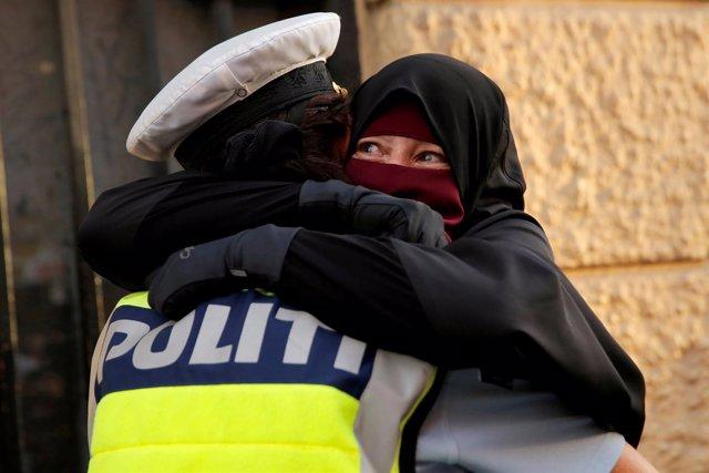 Una policía danesa abraza a una manifestante con niqab en Copenhague