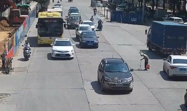 Anciana trata de cruzar una calle con mucho tráfico