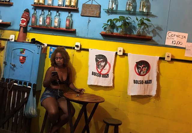 A woman sits next to signs with the image of Brazilian presidential candidate Ja