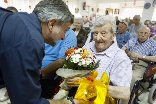 El diputado Ángel Escobar entrega un ramo de flores a Martirio el Día del Mayor.