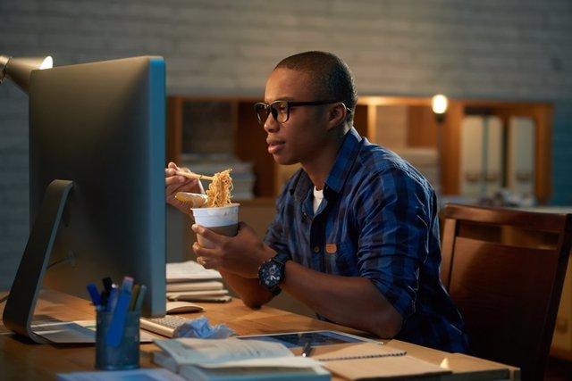 Trabajador comiendo ante un ordenador