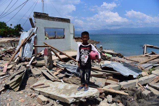 Un niño junto a una vivienda destruida en Palu (Indonesia)