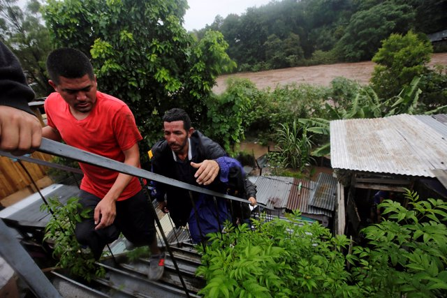 Residents climb stairs nearby the Choluteca river following heavy rains in Teguc