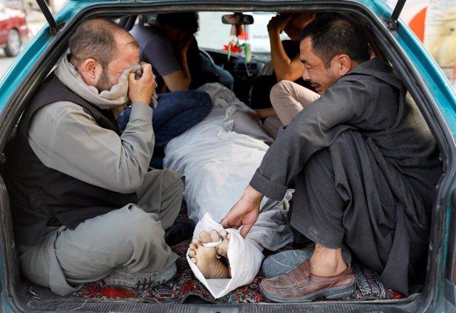 Hombres lloran a una víctima de un atentado en Kabul