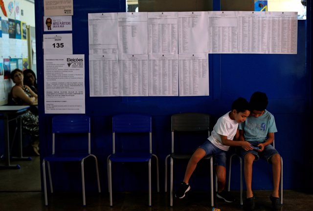 Children sit at a polling station during the presidential election in Brasilia,